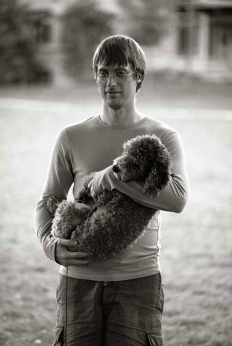 a man cradles a poodle in the park at twilight
