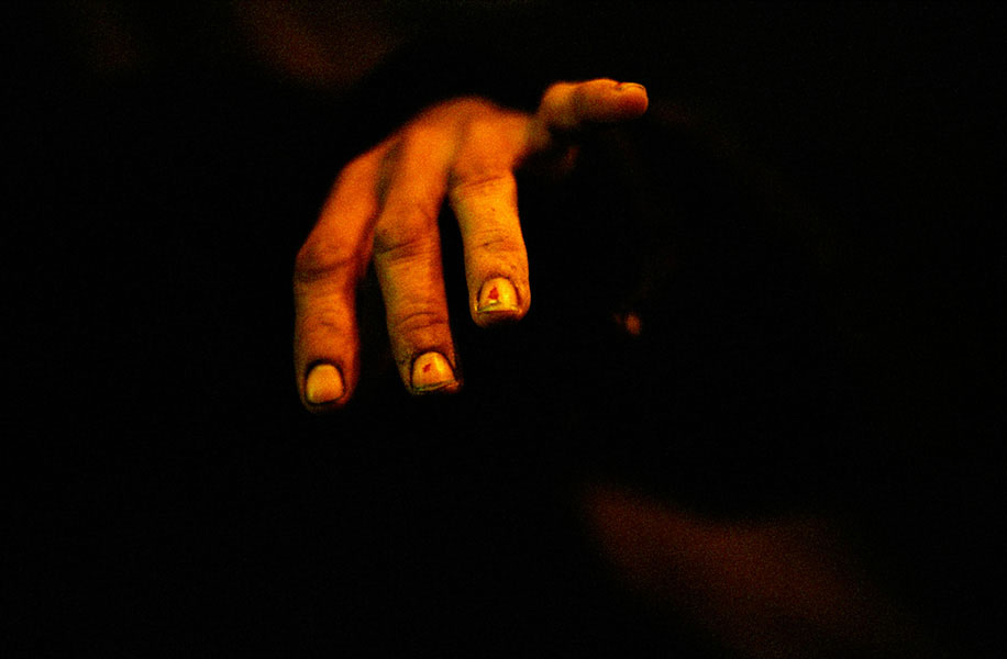 a hand, in an alley, at night
